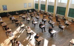 Na zdjęciu uczniowie podczas próbnej matury w trakcie omawiania procedur. Miejsce egzaminu - aula szkolna.